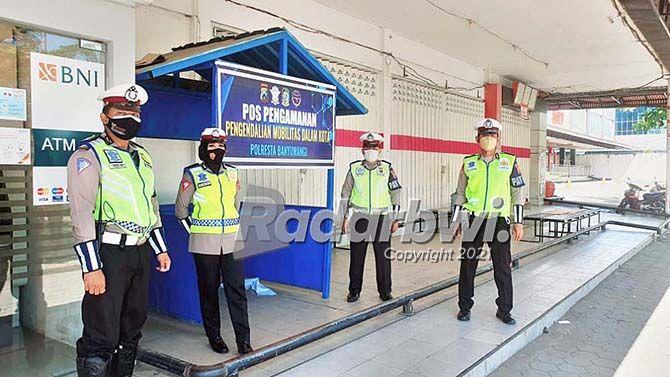 DIJAGA KETAT: Anggota Satlantas Polresta Banyuwangi standby di pos pengamanan pengendalian mobilitas dalam kota yang ada di simpang empat Tugu Pancasila, Banyuwangi, kemarin (27/7).