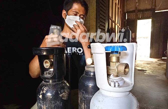 DICARI: Tibyan menunjukkan tabung oksigen yang sudah kosong di tempatnya di Desa Genteng Wetan, Kecamatan Genteng kemarin (28/7).