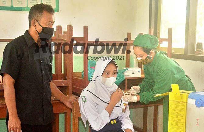 DISUNTIK: Kepala SMPN 4 Muncar Marhenyantoro (kiri) menemani siswanya yang sedang mengikuti vaksinasi di sekolahnya pada Selasa (27/7).