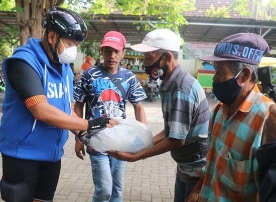 TETAP PROKES: dokter Agung Mulyono saat memberikan paket makanan ke pedagang, tukang becak, warga yang kebetulan melintas di Tamnan Blambangan Jumat, kemarin (30/7).