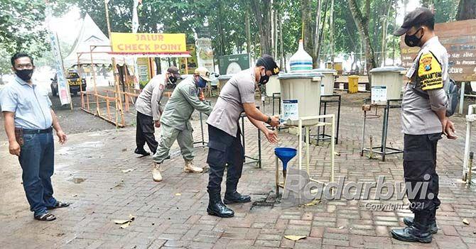 CEK: Anggota Polsek Pesanggaran memeriksa tempat cuci tangan di jalur masuk wisata Pulau Merah, Desa Sumberagung, Kecamatan Pesanggaran kemarin (9/9).