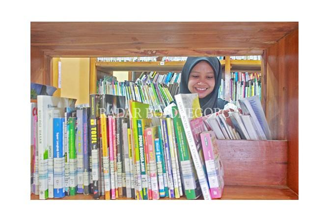 MEMBACA: Salah satu pengunjung membaca buku di perpustakaan.