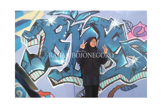 SENI GRAFFITI: Taaliyatu Aayatillah dan hasil coretan di dinding.