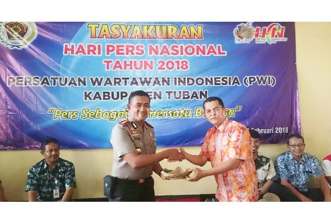 MITRA PERS: Pembina PWI Tuban Dwi Setiyawan menyerahkan potongan tumpeng kepada Kapolres Tuban AKBP Sutrisno HR.