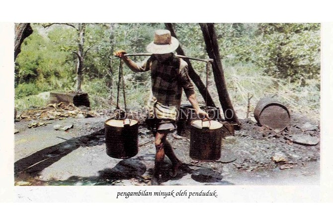 ANGKUT MINYAK: Warga memikul minyak mentah dari sumur minyak tradisional Wonocolo.