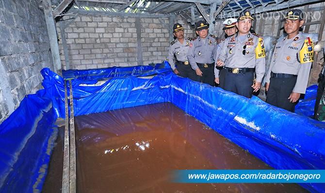MODUS BARU: Kolam berisi bahan baku arak usai dikuras petugas saat digerebek Selasa (1/5).