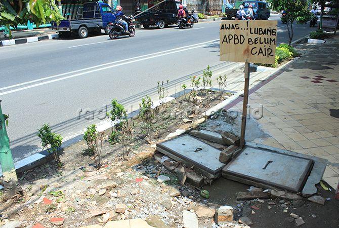 PROTES: Papan kritik yang dipasang warga di trotoar rusak di Jalan Panglima Sudirman.