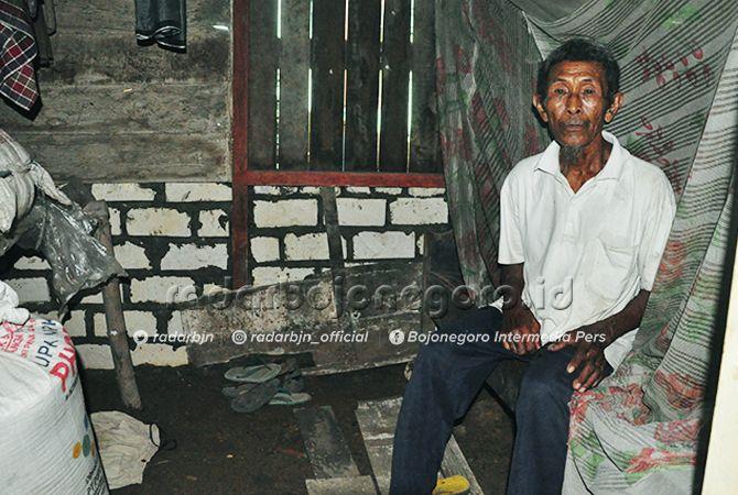 BISA TERSENYUM: Samido dengan rumah barunya yang separo dindingnya tembok.
