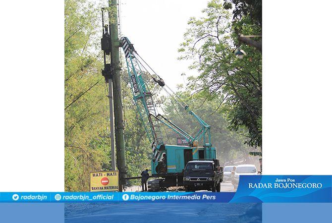 HALANGI SEBAGIAN JALAN: Alat berat yang digunakan pengerjaan tembok penahan tanah di jalur Kecamatan Sugio.
