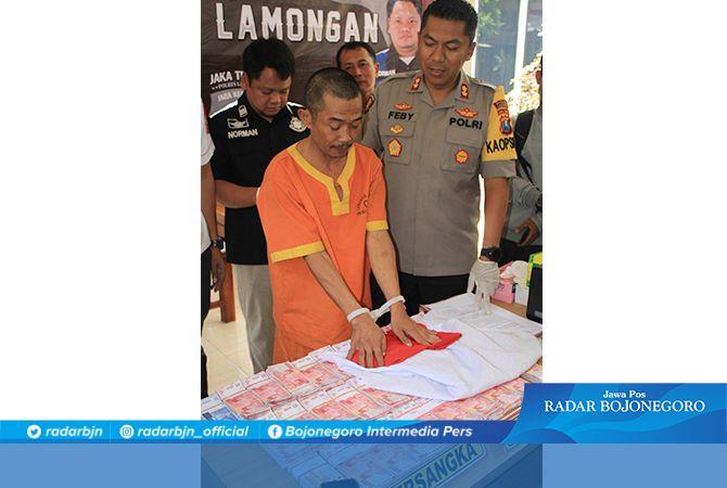 UANG PALSU: Kapolres Lamongan, AKBP Feby DP Hutagalung, meminta tersangka Heri Susanto mempraktikkan cara mengelabui korban agar percaya dengan penggandaan uangnya.
