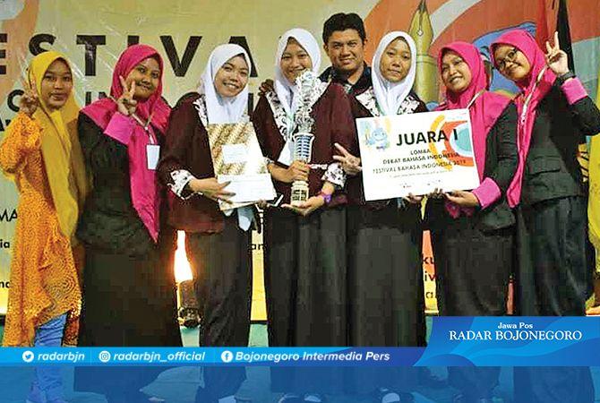 MEMBANGGAKAN: Pembina ekstrakurikuler debat SMKN 2 Tuban Hendra Tonic pose bersama tim debat SMKN 2 Tuban usai meraih juara 1 lomba debat bahasa Indonesia Festival Bahasa Indonesia 2019.