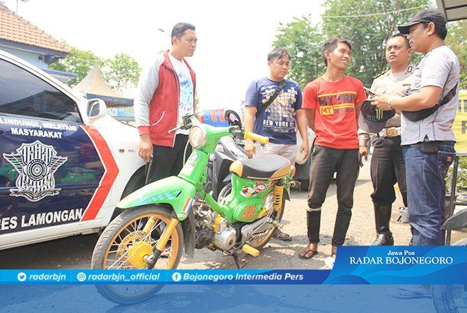 TERTANGKAP: Hasan Nudin Asidik dengan tangan diborgol saat dikeler di Terminal Lamongan usai ditangkap.