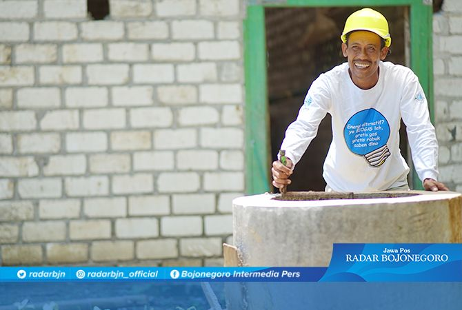 Sutrisno, warga asal Desa Glodog, Palang, Tuban, memproses kotoran sapi dalam reaktor biogas di halaman rumahnya.