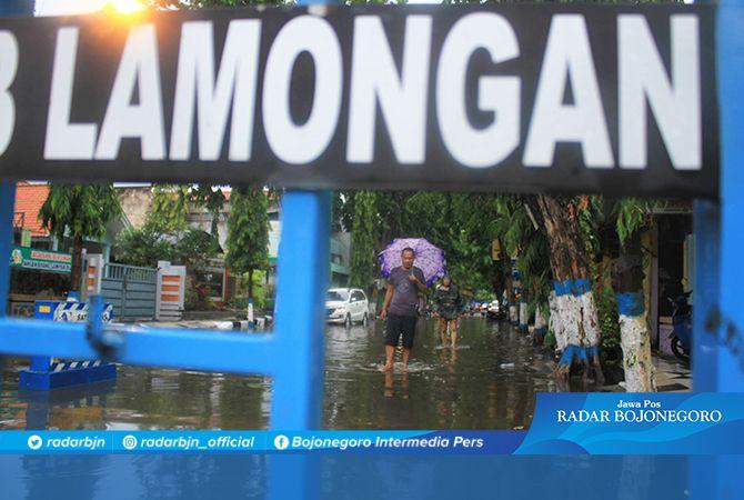 DITUTUP: Warga berjalan kaki di Jalan Dr Wahidin Sudiro Husodo Lamongan yang tergenang akibat diguyur hujan kemarin.