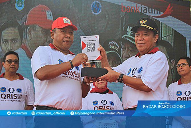 SIMBOLIK: Hartono (kiri), Direktur Perumda Pasar Lamongan menerima barcode Qris dari Bupati Fadeli.