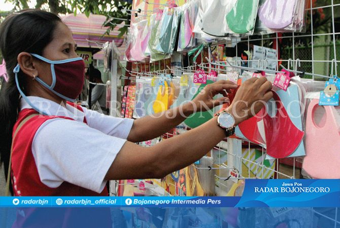 MERUGI: Agustin, seorang PKL menjajakan dagangan masker mangkal di pertigaan ujung Jalan AKBP M. Soeroko, Bojonegoro kemarin (23/9).