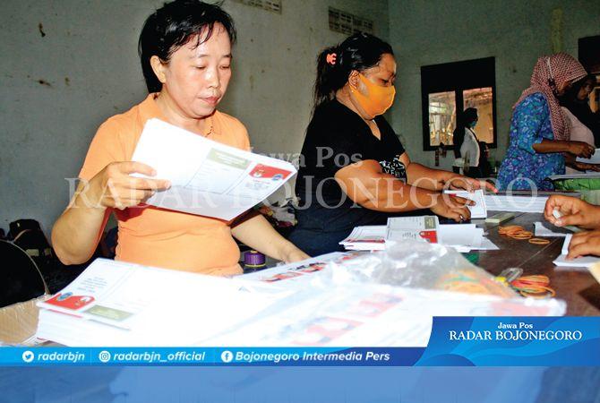 DIKEBUT : Para petugas pelipatan surat suara Pilkada Lamongan sedang ngebut melaksanakan tugas.