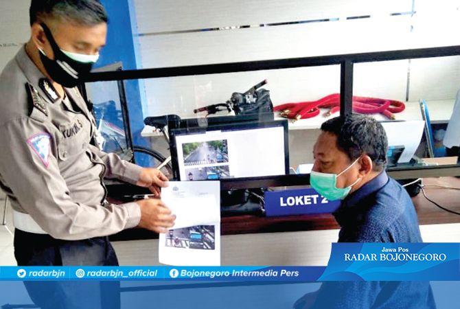 PETUGAS KHUSUS : Salah satu operator Etle di Lamongan sedang menunjukkan bukti rekaman pelanggaran kepada pelanggar lalu lintas.