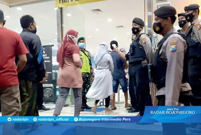 CEK JUMLAH PEMBELI: Petugas kepolisian berjaga di pintu masuk agar tidak terjadi kerumunan.