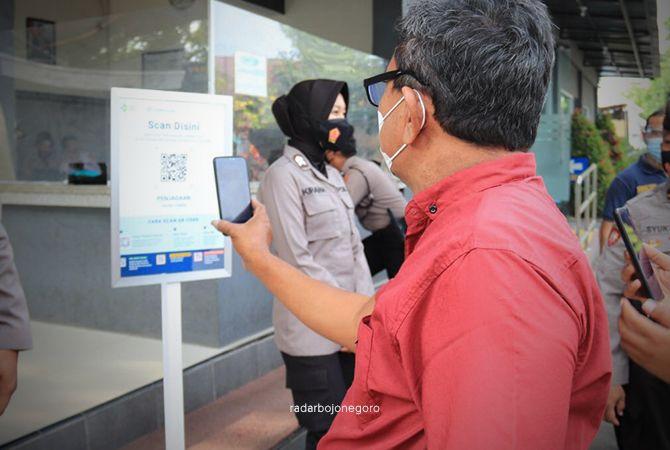 SCAN DULU: Warga yang akan mengurus dokumen ke Polres Tuban diminta scan barcode Peduli Lindungi di pos penjagaan.