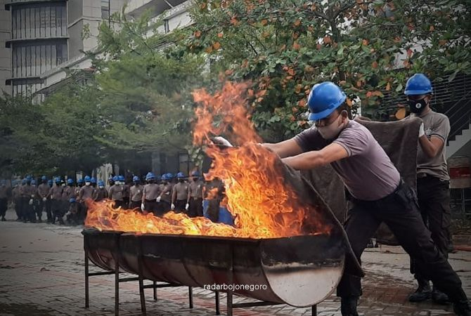 SIAGA: Para sekuriti peserta pelatihan penanggulangan bencana melakukan pemadaman api menggunakan karung.