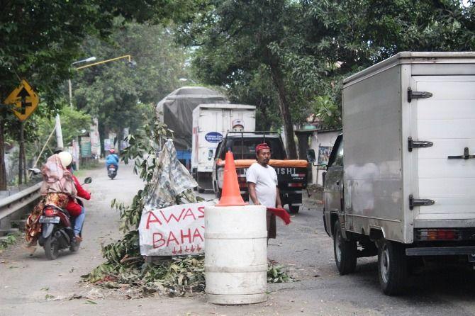 Kondisi jalan nasional tepatnya di Jl Raya Mojoagung rusak berlubang. Warga menandai dengan tong.