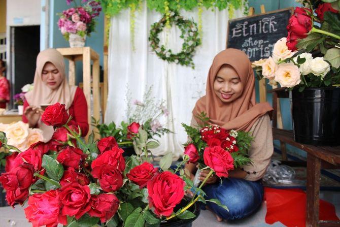 Siti Nur Alfia, 33 dibantu pekerjanya membuat buket bunga untuk acara wisuda kemarin.