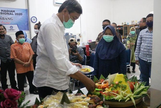 General Manager M Nur Kholis, memotong tumpeng perayaan 6 tahun Jawa Pos Radar Jombang.