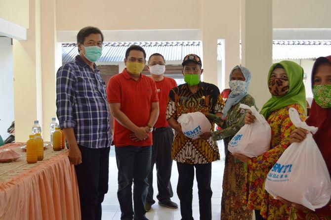 Wakil Bupati Jombang Sumrambah, General Manager Jawa Pos Radar Jombang M Nur Kholis, dan PSMTI Jombang menyerahkan paket sembako kepada warga Desa Plumbon Gambang.