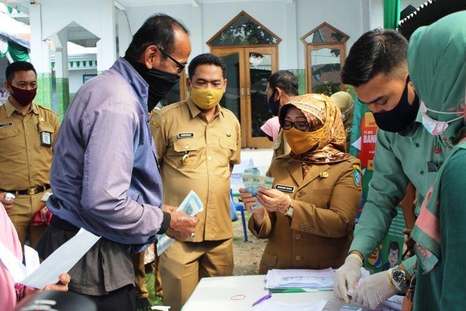 Bupati Jombang Mundjidah Wahab didampingi Wakil Bupati Sumrambah mengecek keaslian uang Bantuan Langsung Tunai (BLT) di Desa Candimulyo.
