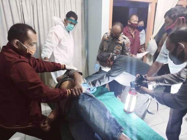Petugas mengamati kondisi jenazah Kasiari, 39, warga Dusun Gedangkeret, Desa Banjardowo, Kecamatan/Kabupaten Jombang yang nekat mengakhiri hidupnya dengan gantung diri.