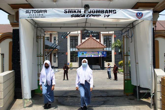 KAWASAN STERIL: Setiap siswa yang masuk di SMKN 1 Jombang wajib melewati bilik disinfektan.