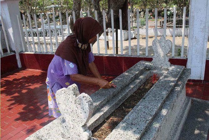 TURUN TEMURUN: Sukarmi, 54, penjaga makam bupati pertama Jombang R.A.A. Soeroadiningrat membersihkan makam kemarin siang.