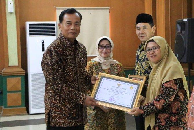 BANGGA: Tri Rochmawati Kepala Perpustakaan SMA DU 2 didampingi Bupati Mundjidah Wahab Jombang menerima akreditasi perpustakaan.