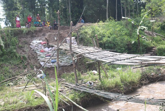 Warga membangun jembatan sementara dari bambu di Sungai Konto.