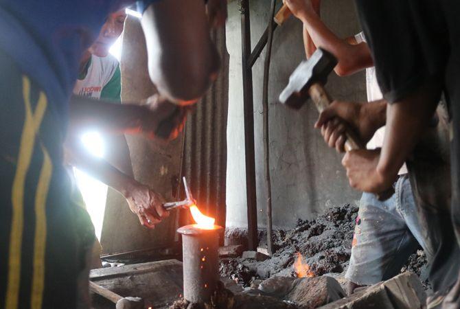 MANUAL: Sejumlah perajin dI Dusun Doro, Desa Karangdagangan, pandai besi tengah menyelesikan produk alat pertanian.