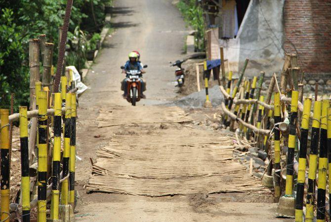 AWAS LICIN: Sejumlah warga melintas di Jembatan darurat di Desa Banjaragung kemarin (21/2).