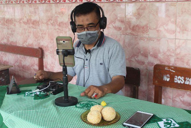 SERIUS: Ngadimin menggunakan headphone dan perangkat rekaman untuk menyampaikan materi kepada siswa melalui pesan suara.