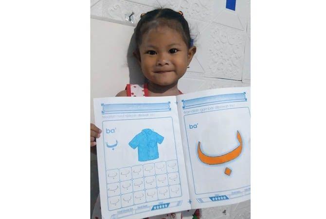 LUCU: Umi Nur Laili, siswa KB Mutiara Hati menunjukkan karya mewarna dan menebali huruf, kemarin.
