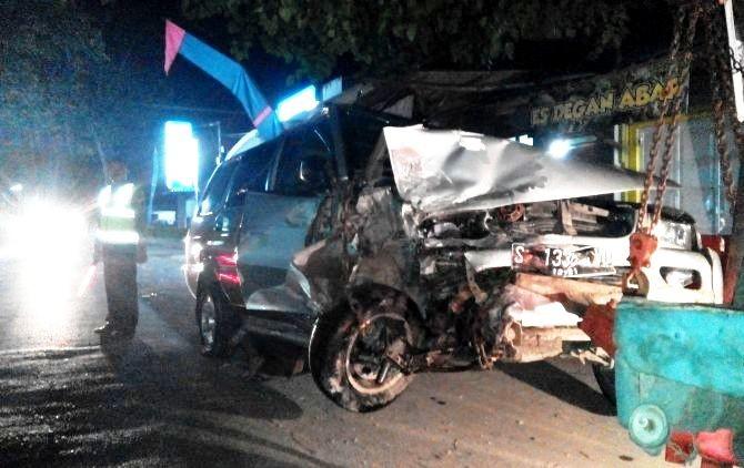 EVAKUASI: Petugas mengatur lalu lintas selama proses evakuasi mobil yang terlibat kecelakaan Sabtu malam (16/6).