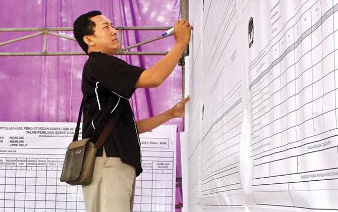 CATAT HASIL: Petugas PPK Nganjuk merekap ulang perolehan suara dari tiap PPS disaksikan panwascam dan saksi pasangan calon bupati.