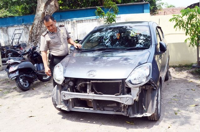 RUSAK : Petugas Polsek Pagu memperlihatkan barang bukti berupa mobil penyebab kecelakaan di Jalan Raya Desa Bangsongan, Kecamatan Kayenkidul, kemarin.