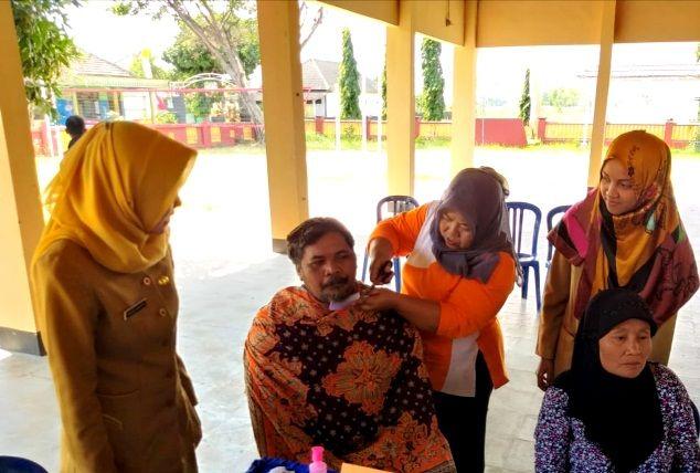 MERAPIKAN: Seorang petugas posyandu Jiwa Desa Semen, Pagu, memotong jenggot salah seorang pasien binaan.
