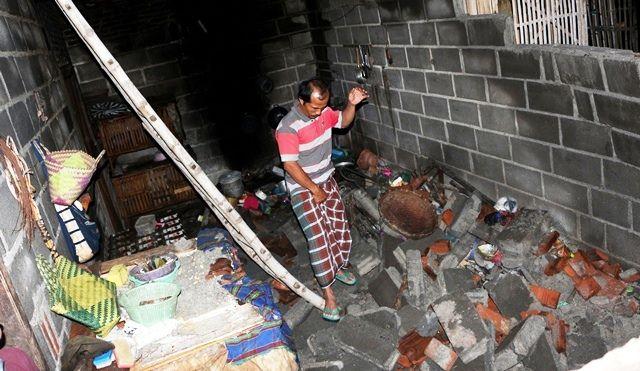 MERANA: Imam Muksin berjalan di antara reruntuhan tembok dan genting rumahnya, pasca-angin kencang menerjang desanya kemarin.