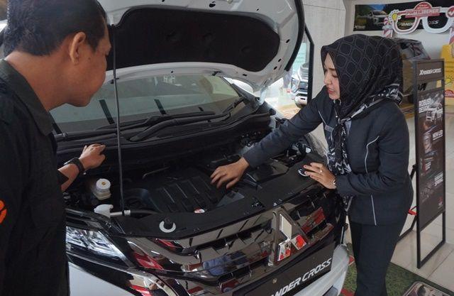 GACOAN BARU: Eva (kanan), sales promotion PT Sun Star Motors Kediri, menjelaskan spesifikasi mesin Xpander Cross kepada pengunjung di dilernya (15/1).