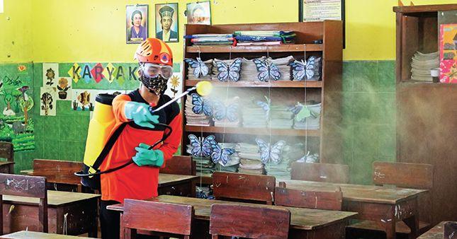 SEMPROTI SEKOLAH : Petugas dari BPBD Kota Kediri melakukan penyemprotan disinfektan di SD Pojok, Kecamatan Mojoroto kemarin pagi.