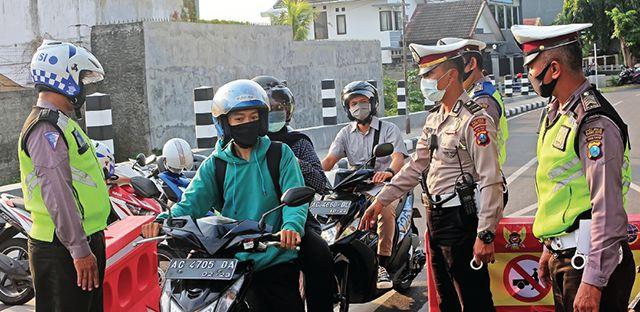 BERGANTIAN : Polisi menghentikan pengendara yang hendak melewai Jalan Inspeksi Brantas kemarin sore.