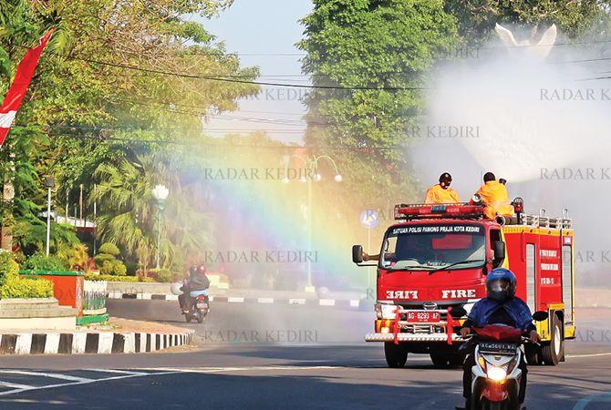 BERKABUT : Tim gabungan dari damkar, DLHKP, dan BPBD Kota Kediri menyemproti jalan-jalan dengan cairan disinfektan kemarin.