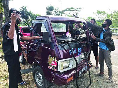 RINGSEK: Warga dan pengendara membantu evakuasi pikap yang ringsek setelah menabrak mobil milik Sakur, 30, saat parkir di depan SPBU Baron kemarin sore.