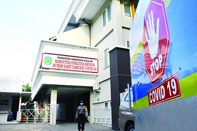 PROTOKOL KETAT: Salah seorang anggota polisi keluar dari RS Darurat Pu Sindok kemarin siang. Gedung yang disulap jadi tempat perawatan pasien Covid-19 ini dijaga dengan ketat.